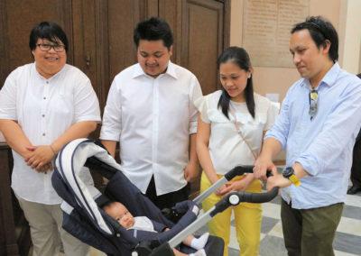 Il piccolo Paolo, sotto lo sguardo compiaciuto del papà, della mamma, del padrino e della madrina
