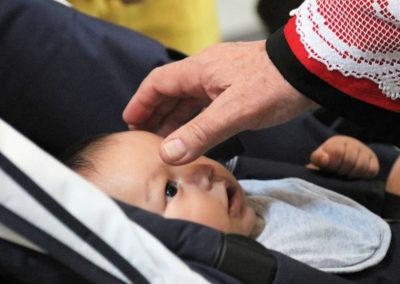 Segno di croce del celebrante sulla fronte del bambino